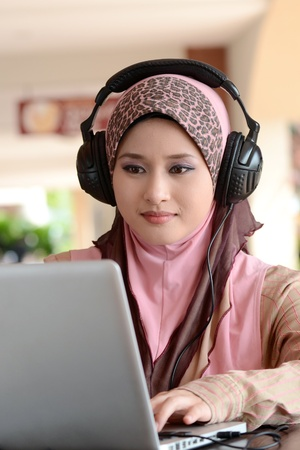 Young pretty Asian muslim woman in head scarf listens to audio with headphone while working on laptop in cafe