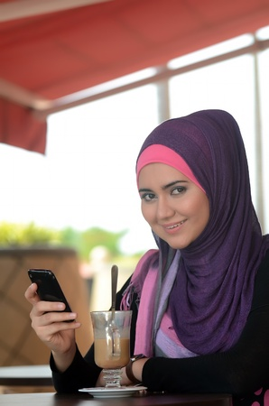 young muslim woman in head scarf using phone in cafe