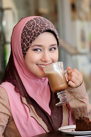 Pretty young Asian Muslim woman with lovely smiles having lunch at coffee shop