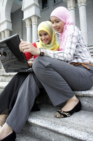 Young pretty Asian muslim college girls having discussion with book and laptop.