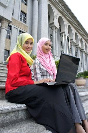 laptop asian: Las j�venes musulmanas de Asia bonita de la universidad que tiene el debate con el libro y el ordenador port�til. Foto de archivo