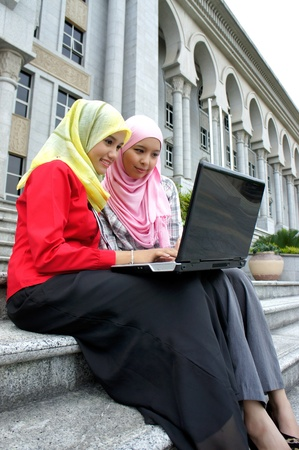 Young pretty Asian muslim college girls having discussion with book and laptop. photo