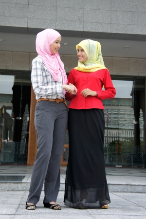 malay ethnicity: Two young pretty Asian muslim business woman in head scarf shake hand togethe