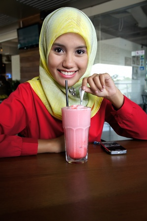 Close-up portrait of beautiful young Asian Muslim woman at cafe with lovely smiles photo