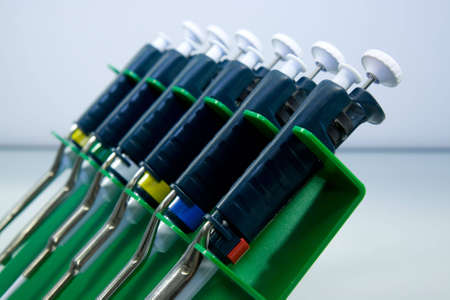 biochemical: Set of mechanical pipettes in a green plastic holder