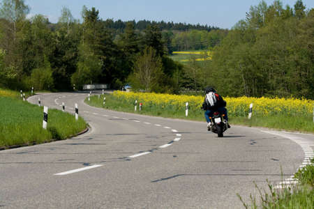 On the road. Motorcycle on the rural road. Blooming yellow field next to the road. Switzerland Stock Photo - 4495830