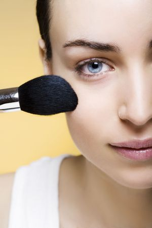 Young woman applying makeup with brush photo