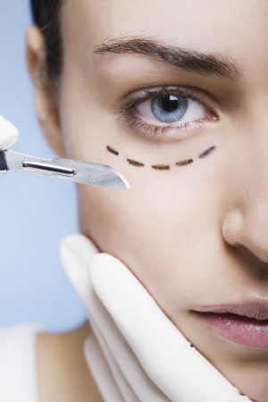 cosmetic surgery with scalpel on a young woman photo