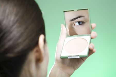 young woman looking into a mirror to check her make up photo