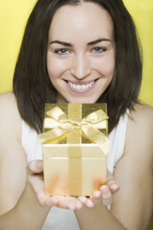 beautiful young woman presents a gift photo