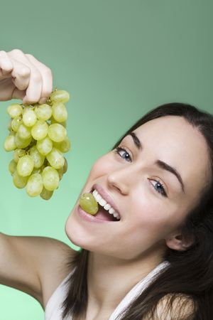 woman enjoys eating grapes and turns arround  photo