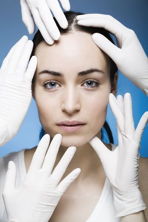 rubber gloves touching womans face Stock Photo
