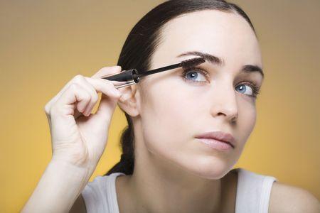 young woman applying mascara on her