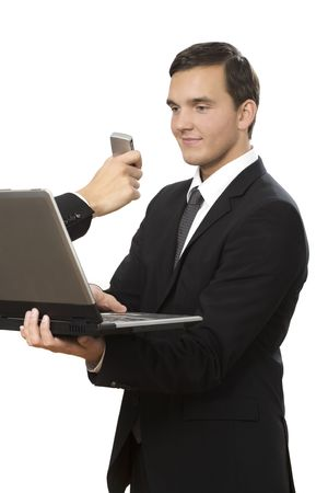 hand reaches out of laptop towards young businessman holding a cellphone Stock Photo - 6090799