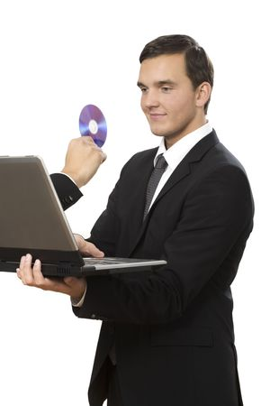 hand reaches out of laptop towards young businessman holding a disc photo