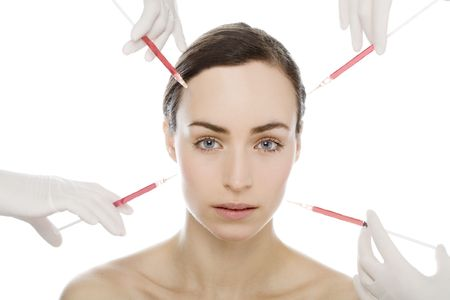young woman gets botox injection from many syringes photo