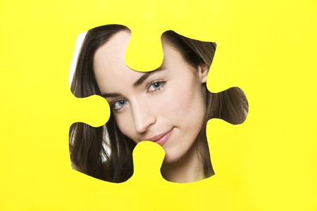 woman looks through puzzle shape photo