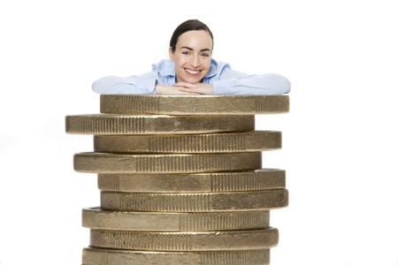 young business woman leaning against a stack of euros