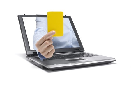 a hand reaches out of a laptop and shows a yellow card