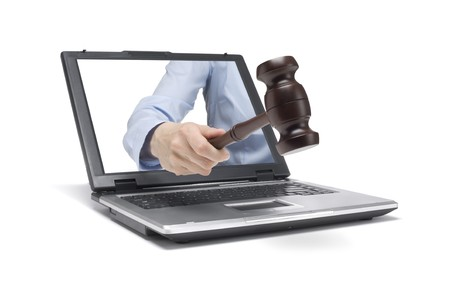 legislation: a hand reaches out of a laptop with a wooden hammer