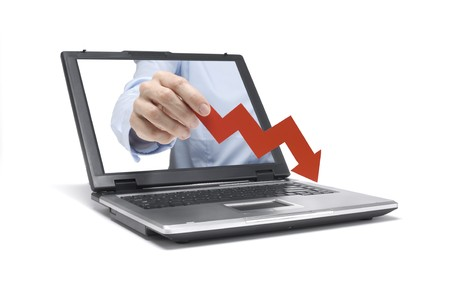 A Hand reaches out of an Laptop with a downwards graph Stock Photo - 7143976