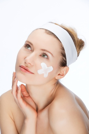 young woman with skin cream on her face