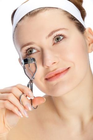 young beautiful woman cutting her eye lashes