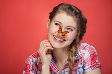 young woman watching butterfly on her nose Stock Photo