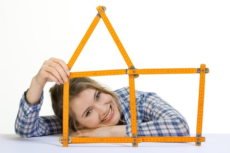young woman forms meter stick into a house shape Stock Photo
