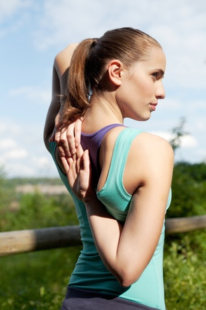 attractive young sportswoman stretching and warming up