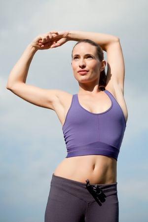 attractive young sportswoman stretching and warming up Stock Photo - 10699170
