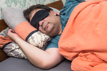 adult man in black mask sleeps on bed in daytime