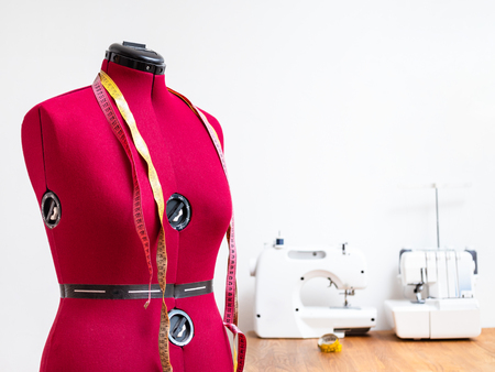 red dummy with two measuring tapes in dressmaker workshop