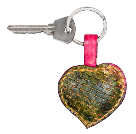 door key on handmade green colored embossed leather heart shaped key fob cutout on white background