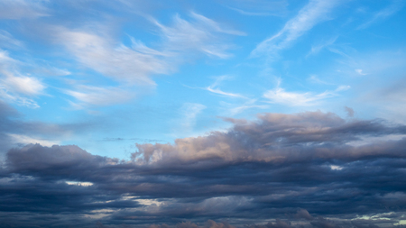 white spindrift clouds in blue sky over black clouds in autumn evening Stock Photo