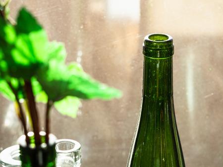empty green wine bottle near windows illuminated by sun at home