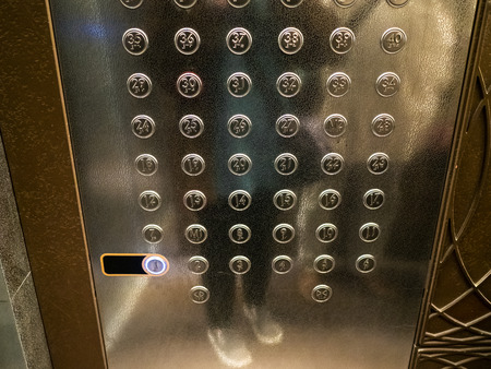panel with many buttons in modern passenger elevator of high-rise building