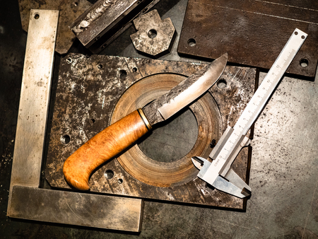 Metalworking still life - top view of forged knife and calliper on metal workbench in turnery workshop in warm yellow light