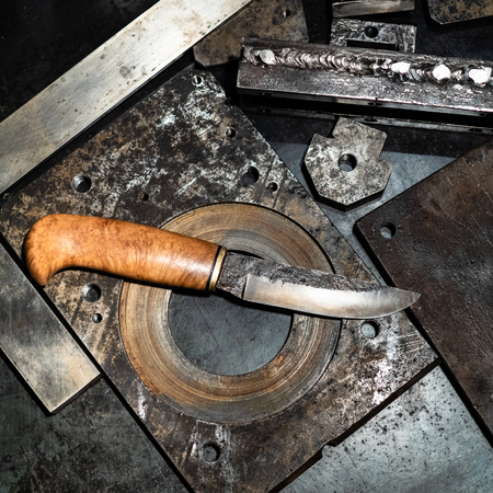 Metalworking still life - top view of forged knife with wooden handle on metal workbench in turnery workshop Zdjęcie Seryjne