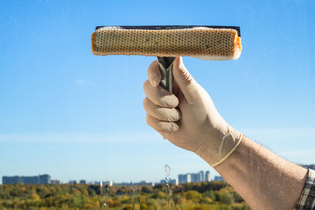 male hand washes a home window glass in city in sunny autumn day