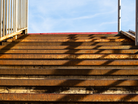 rusty steps of metal outdoor stairs in sunny day 免版税图像