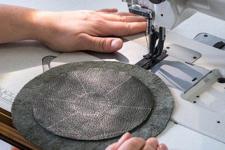 workshop of making the leather bag for jewelry - craftsman prepares to sew the details of pouch with cutting pattern on sewing machine