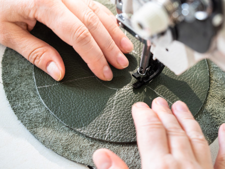 workshop of making the leather bag for jewelry - craftsman sews a circle on pouch with cutting pattern on sewing machine