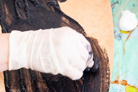 workshop of making the carved leather bag - craftsman stains the stamped leather for handbag