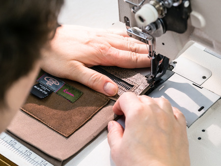 workshop of making the carved leather bag - craftsman sews the inner pocket for leather handbag on sewing machine Stockfoto