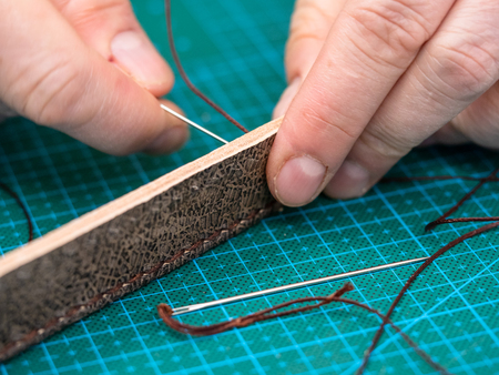 workshop of making the carved leather bag - craftsman stitches the carved brown belt for leather handbag by needle with thread