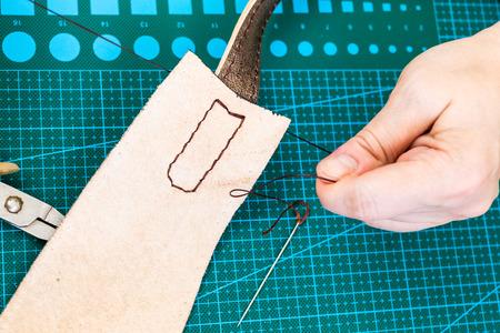 workshop of making the carved leather bag - craftsman fixes stitch on the belt for leather handbag