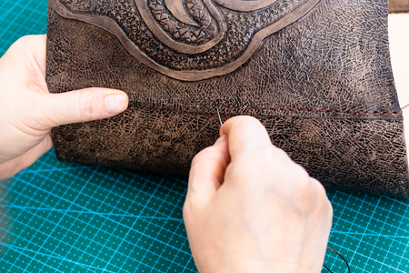 workshop of making the carved leather bag - craftsman sews the flap to the leather handbag