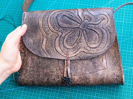 workshop of making the carved leather bag - craftsman shows the carved flap of the handbag Stock Photo