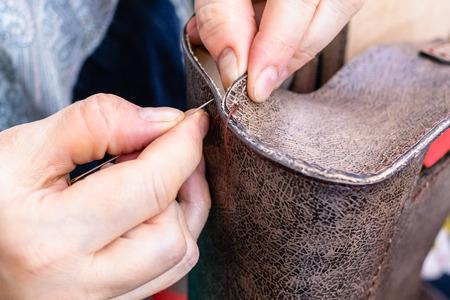 atelier de fabrication du sac en cuir sculpté - artisan coud le bord latéral du sac à main